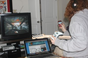 Teenager Playing Guitar while Playing Video Game, Texting, and using computer