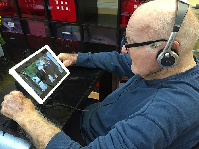 Elderly iPad user watching 60 minutes with headphones
